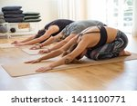 people doing child pose on mats ... | Shutterstock . vector #1411100771