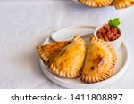 Small photo of Homemade Spanish Empanadillas, small filling tuna pies served with tomato souse. Typical dish in Latin American and Spain cuisine.
