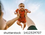 Father hands holding up infant baby outdoor Fathers day holiday happy family lifestyle dad and daughter together