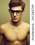 Beautiful (handsome) muscular male model with nice body wearing trendy glasses and posing over light-gray background. Hipster and vintage (retro) style. Close up. Studio portrait. - stock photo