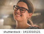 Small photo of Close up Portrait A young woman wearing glasses smiling inadvertently laughing and white teeth because she was hit by a friend's hand on the shoulder to feel ticklish. : Selective Focus