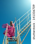Outdoors portrait of a woman in airy crimson dress on the old metallic construction, blue sky background - stock photo