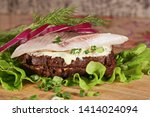 Stock photo sandwich with herring red onion rye bread on a brown table tradition danish open sandwich 1414024094
