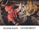 Heavy Duty Mining Dump Truck Differential Problem. Caucasian Driver Trying to Bush Fix. Heavy Duty Equipment Problem. - stock photo