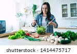Small photo of Beautiful young woman is preparing vegetable salad in the kitchen. Healthy Food. Vegan Salad. Diet. Dieting Concept. Healthy Lifestyle. Cooking At Home. Prepare Food. Cutting ingredients on table