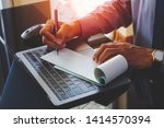 Small photo of Businessman hand writing and signing white empty bank checkbook with modern computer notebook and wireless mouse on the desk at office. Payment by check,paycheck,payroll ,cheque sign conceptual.