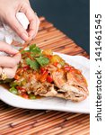 Food stylist garnishing Thai style whole fish red snapper dinner with tamarind sauce on a white fish shaped plate. Shallow depth of field. - stock photo