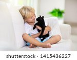 Stock photo child playing with baby cat kid holding black kitten little boy snuggling cute pet animal sitting 1415436227