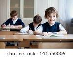 happy schoolboys sitting at... | Shutterstock . vector #141550009