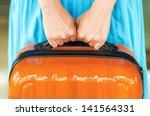 woman in blue dress holds... | Shutterstock . vector #141564331