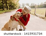 Stock photo lovely blonde kissing her dog tenderly on the autumn park path stylish girl feels good under the 1415931734