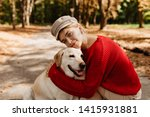 Stock photo lovely young woman in nice light hat and red sweater sitting with labrador together in the autumn 1415931881