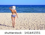 Sexy woman on the beach in a sunny day with blue sky and clear sand with white hat from back - stock photo