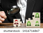 Small photo of Businessman with a magnifying glass examines puzzle with an incompetent and toxic worker. The concept of the organization of the team and the business hierarchy. Management. appointment of the head