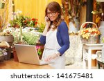 smiling mature woman florist... | Shutterstock . vector #141675481