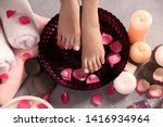 Stock photo woman soaking her feet in bowl with water and rose petals on floor top view spa treatment 1416934964