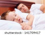 father and baby sleep in bed | Shutterstock . vector #141709417