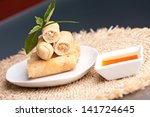 Plate of Thai spring rolls appetizer with garnish. Shallow depth of field. - stock photo