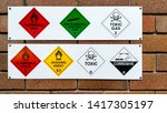 Small photo of A series of flammable, non-flammable, toxic, corrosive and oxidizing gas and chemical safety symbols attached to a brick wall for public safety and cautionary purposes.