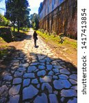 Young woman walks on stone path of  ancient Roamn road Via Appia Antica in vanishing point in big park area in Rome, Italy