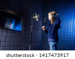 girl star singer artist in a black blouse with headphone recording new song with microphone. - stock photo