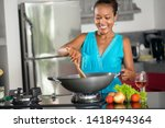 Small photo of Smiling Indonesian woman stirring food in wok in kitchen