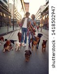 Stock photo dog walking on leash with professional dog walker couple on the street 1418502947