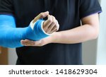 Small photo of Closeup of asian man's arm with long arm plaster, fiberglass cast therapy cover by blue elastic bandage after sport accident. Appropriate treatment in western medicine.