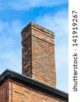 An Old Brick Chimney With Blue...