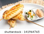 Asian style chicken satay barbecued chicken on skewers with peanut dipping sauce. - stock photo