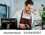 Stock photo barista young man scanning qr code or barcode in menu paper at counter in cafeteria new payment 1419650507