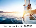 sunrise sailing man on boat in... | Shutterstock . vector #141987769