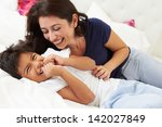 mother and son lying in bed... | Shutterstock . vector #142027849