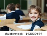 happy pupil in uniform sitting... | Shutterstock . vector #142030699
