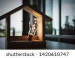 Small photo of Light bulb with wood house on the table, a symbol for construction, Creative light bulb idea, power energy or business idea concept ecology, loan, mortgage, property or home.