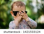 Stock photo little baby playing bo peep girl hiding face summer background sunglasses 1421533124