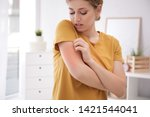 Small photo of Woman scratching arm indoors, space for text. Allergy symptoms