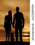 Stock photo a silhouette of a man and woman holding hands while their pet dog sits between them 142209454