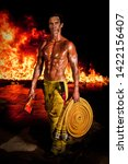 Small photo of A rugged and muscular firefighter with an axe and firehose in hands and raging fire in the background. Fireman calendar.