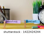 Small photo of Regulations and Guidelines. Handwriting on sticky notes in clothes pegs on wooden office desk