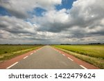 Small photo of Road in Holland with red cycle path on both sides, perspective, under heavy dark threatening cloudy skies and between green meadows and a faraway straight horizon.