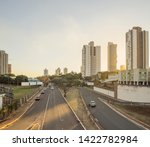 Two lanes avenue with few cars, trees, blank advertising billboards, and buildings around. Sunset at the large avenues of the capital city Campo Grande - MS, Brazil. Ricardo Brandao avenue.