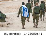 Back shot of several soldiers of israel army walking with an israel national flag. Military man bearing israel flag on his shoulder walking with other soldiers. Military games. War tactical exercise