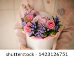 Small photo of Girl holding a spring box of tender pink and violet flowers decorated with green leaves