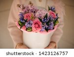 Small photo of Girl holding a white spring box of tender pink and violet flowers decorated with green leaves