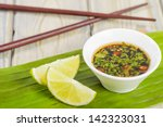 Stock photo southeast asian dipping sauce with chilli coriander and fish sauce and lime wedges 142323031
