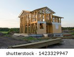 Skeleton of a wooden two-story cottage, partially wired with OSB panels, surrounded by building materials and garbage. Unfinished country house in rays of setting sun in the background of the forest - stock photo