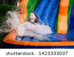 Small photo of Young girl splashing into the bottom of a water bouncy slide.