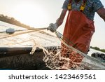 Small photo of Dynamic composition with a fisherman dressed in an orange rompers gathering his trammel net during a fishing trip on the Danube river.