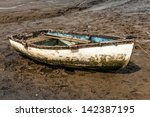 single old muddy rowing boat at ... | Shutterstock . vector #142387195